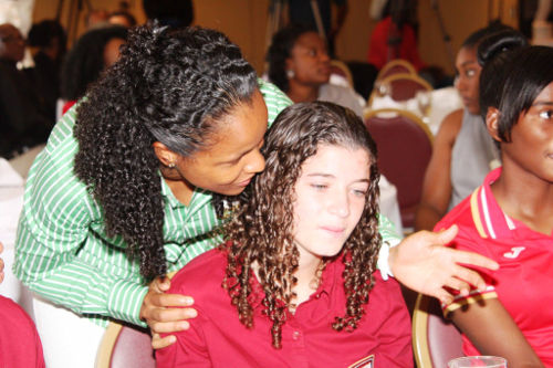 Photo: Trinidad and Tobago star Maylee Attin-Johnson (left) has a word with teenaged striker Anique Walker (centre) during a function. (Courtesy SPORTT)