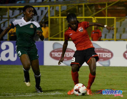Photo: Trinidad and Tobago star attacker Kennya Cordner (right) goes for goal while St Kitts defender Rozel Liburd looks on. (Courtesy Jinelle James/Wired868)