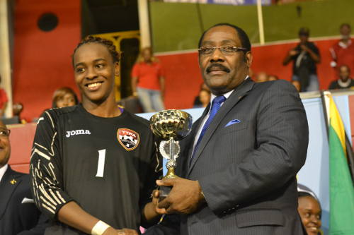Photo: Trinidad and Tobago goalkeeper Kimika Forbes (left) receives the 2014 Caribbean Cup Best Goalkeeper prize from CFU executive member Horace Burrell. (Courtesy Jinelle James/WOLF)