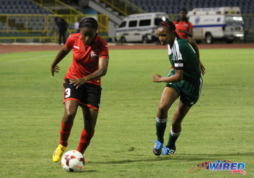 """Photo: Trinidad and Tobago attacker Mariah Shade (left) runs at St Kitts and Nevis captain Shandor Wilkinson during the 2014 Caribbean Cup opener. Shade scored a vital double against Antigua and Barbuda to take the """"Soca Princesses"""" into CONCACAF. (Courtesy Jinelle James/Wired868)"""