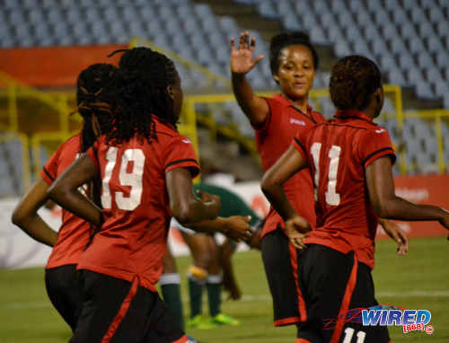Photo: Trinidad and Tobago captain Maylee Attin-Johnson (second from right) is congratulated by teammates after scoring in their 10-0 rout of St Kitts and Nevis. (Courtesy Jinelle James/Wired868)