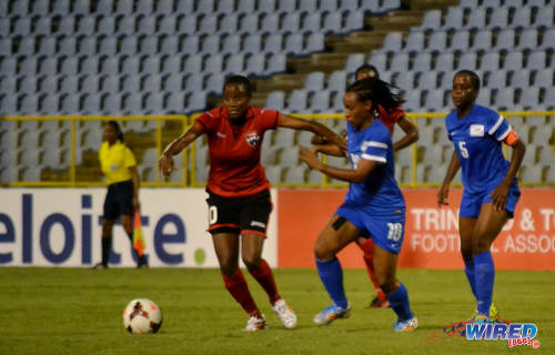 Photo: Trinidad and Tobago attacker Tasha St Louis (far left) holds off Martinique midfielder Christine Gamot. (Courtesy Jinelle James/Wired868)