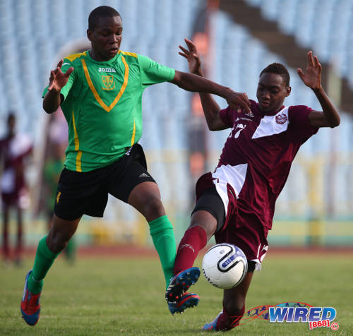 Photo: East Mucurapo Secondary forward Kathon St Hillaire (right) tries to keep the ball from St Benedict's defender Rondell Payne during a SSFL Premier Division clash. (Courtesy Allan V Crane/Wired868)