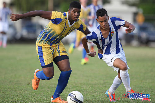 Photo: St Mary's College winger Sebastien Cabral (right) tries to get away from Fatima College defender Mossiah Griffith. (Courtesy Allan V Crane/Wired868)