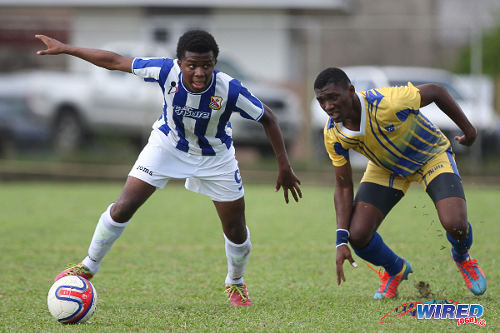 Photo: St Mary's College striker Chinua Bernard (left) troubles Fatima College defender Andrew Abraham during 2014 SSFL Premier Division action. (Courtesy Allan V Crane/Wired868)