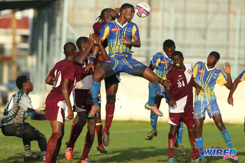 Photo: Fatima College defender Adrian Constantine (centre) contests an aerial ball against East Mucurapo today. (Courtesy Allan V Crane/Wired868)
