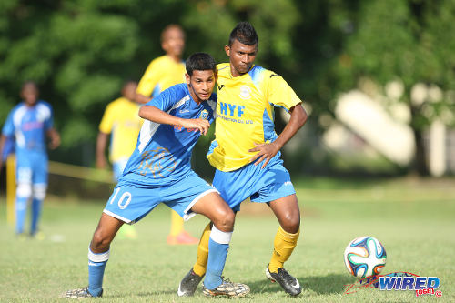 Photo: Presentation College (San Fernando) midfielder Kyle Moodie (left) tries to hold off Shiva Boys left back Jerry Ramdeo. (Courtesy Allan V Crane/Wired868)