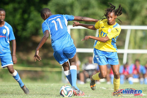 "Photo: Shiva Boys midfielder Tyrel ""Pappy"" Emmanuel (right) dribbles past Presentation College (San Fernando) midfielder Kareem Riley during 2014 SSFL action. (Courtesy Allan V Crane/Wired868)"