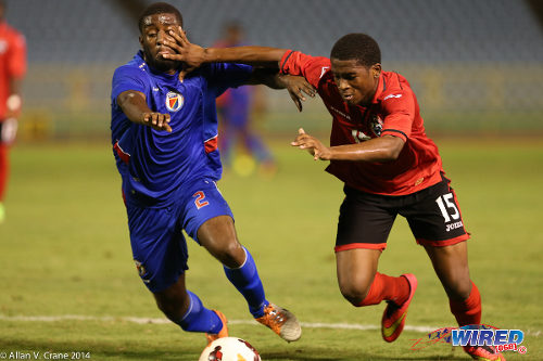 Photo: Trinidad and Tobago winger Aikim Andrews (right) forces his way past Haiti defender Stephane Lambese during the 2014 Under-20 Caribbean Cup. (Courtesy Allan V Crane/Wired868)