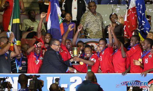 Photo: Trinidad and Tobago National Under-20 captain Shannon Gomez (centre) takes the 2014 Caribbean Cup trophy from CFU president Gordon Derrick. (Courtesy Allan V Crane/Wired868)
