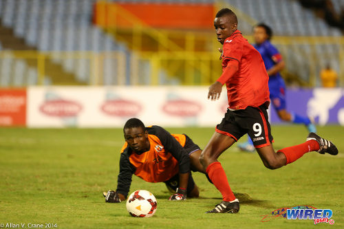Photo: Trinidad and Tobago under-20 striker Kadeem Corbin (right) prepares to fire past Haiti goalkeeper Steve Sanon in the 2014 U-20 Caribbean Cup final. (Courtesy Allan V Crane/Wired868)