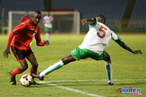 Photo: Trinidad and Tobago striker Kadeem Corbin (left) eludes Suriname defender Nigel Zandveld during an 2014 Under-20 Caribbean Cup fixture. (Courtesy Allan V Crane/Wired868)
