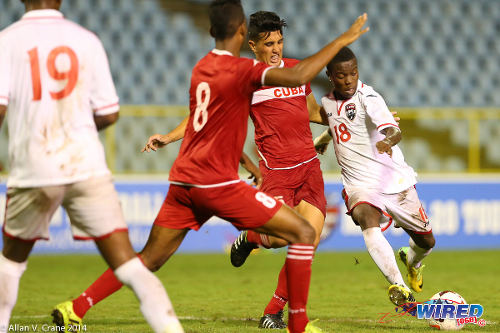 Photo: Trinidad and Tobago national under-20 midfielder Jabari Mitchell (right) tries to squeeze a shot past two Cuban defenders during the 2014 Caribbean Cup. (Courtesy Allan V Crane/Wired868)