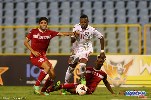 Photo: Trinidad and Tobago winger Levi Garcia (centre) steams past Cuba players Yendri Torres (right) and Roberto Peraza during the Under-20 Caribbean Cup. (Courtesy Allan V Crane/Wired868)