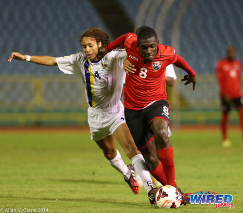 Photo: Trinidad and Tobago midfielder Neveal Hackshaw (right) holds off Curaçao defender Luivienno Statia during the 2014 U-20 Caribbean Cup. (Courtesy Allan V Crane/Wired868)