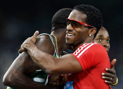 Photo: Trinidad and Tobago former Olympic star Ato Boldon (right) hugs an unidentified Nigerian sprinter during his track hey-day. (Copyright AFP 2014/Jeff Haynes)