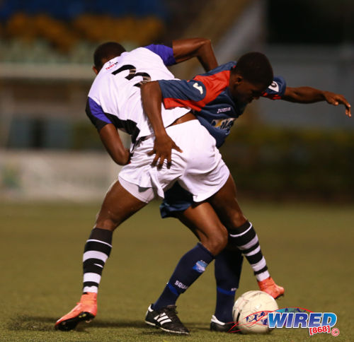 "Photo: Caledonia AIA midfielder Jameel ""Shotta"" Neptune tries to find a way past North East Stars player Kareem Richardson in the First Citizens Cup quarterfinal. (Courtesy Allan V Crane/Wired868)"