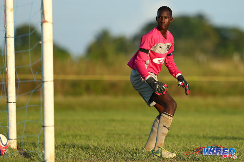 Photo: Carapichaima East Secondary goalkeeper Dejourn Charles looks for the ball after a free kick from Naparima College midfielder Jabari Mitchell. (Courtesy Allan V Crane/Wired868)