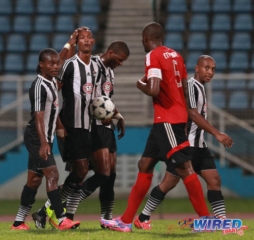 Photo: Central FC midfielder Ataulla Guerra (second from left) celebrates with his teammates while Point Fortin Civic defender Andre Ettienne looks on. Leston Paul (far right) joins Guerra in the national team for the 2014 Caribbean Cup finals. (Courtesy Allan V Crane/Wired868)