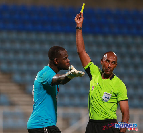 Photo: Referee Neal Brizan (right) cautions Central FC goalkeeper Jan-Michael Williams for dissent during their Pro League encounter with W Connection. (Courtesy Allan V Crane/Wired868)