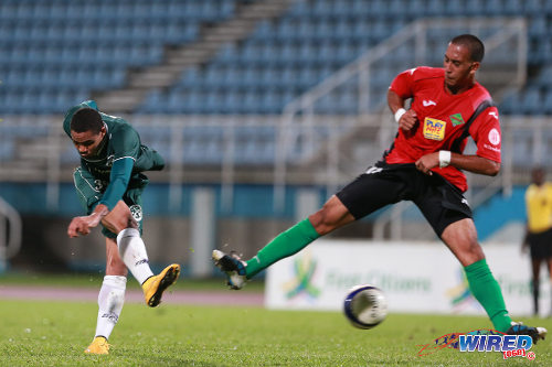 Photo: W Connection right back Alvin Jones (left) fires his shot past San Juan Jabloteh left back Calib Sturge during 2014 First Citizens Cup action. (Courtesy Allan V Crane/Wired868)