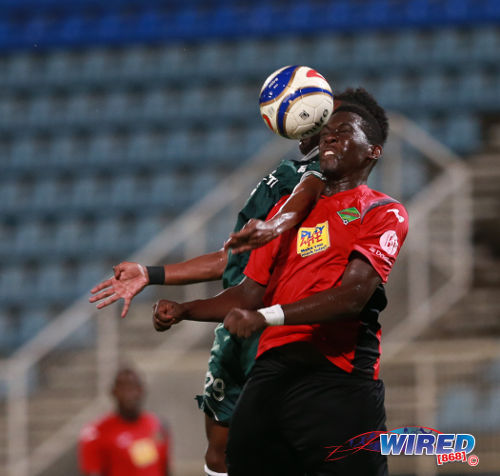 Photo: San Juan Jabloteh defender Dario Holmes (foreground) wins an aerial challenge with W Connection winger Akeem Garcia in the First Citizens Cup. (Courtesy Allan V Crane/Wired868)