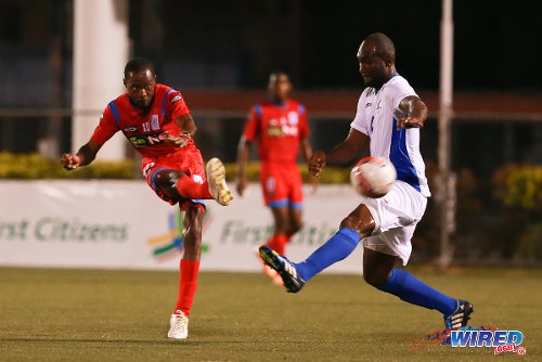 Photo: St Ann's Rangers attacker Kennedy Isles (left) curls home past Police FC defender Karlon Murray in the First Citizens Cup quarterfinal. (Courtesy Allan V Crane/Wired868)
