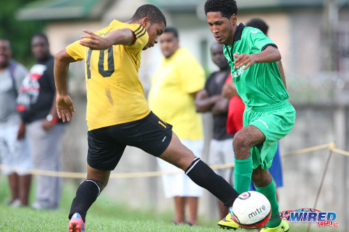 Photo: San Juan North midfielder Romario Rochard (right) dribbles past St Benedict's College utility player Shemar Ravello in Premier Division action at Bourg Mullatrasse. (Courtesy Allan V Crane/Wired868)
