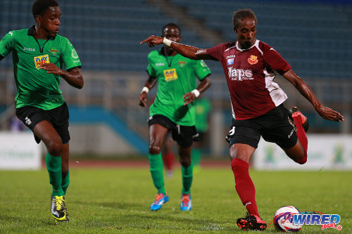 Photo: North East Stars attacker Tyrone Charles (right) goes for goal against San Juan Jabloteh in the 2014 First Citizens Cup semifinal. (Courtesy Allan V Crane/Wired868)