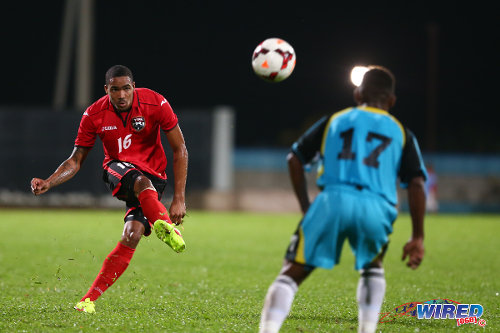 Photo: Trinidad and Tobago right back Alvin Jones (left) drives the ball into the opposing penalty area while St Lucia player Romiel Felix looks on. (Courtesy Allan V Crane/Wired868)