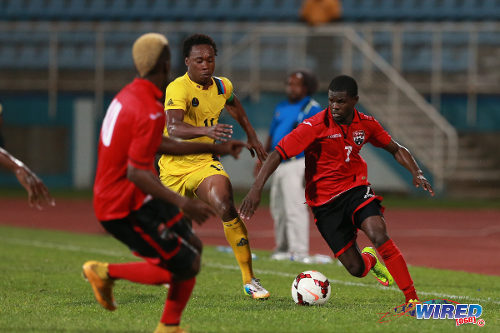 Photo: Trinidad and Tobago midfielder Hughtun Hector (right) advances while Antigua and Barbuda defender Quinton Griffith (centre) and Kevin Molino watch on during the 2014 Caribbean Cup qualifying round. (Courtesy Allan V Crane/Wired868)