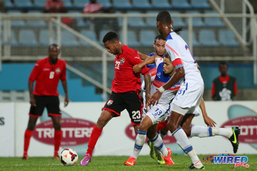 Photo: Trinidad and Tobago winger Lester Peltier (second from left) prepares to fly past a trio of Dominican Republic defenders in last night's Caribbean Cup qualifier in Couva. (Courtesy Allan V Crane/Wired868)