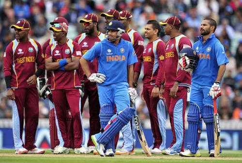 Photo: India cricketer Rohit Sharma (centre) waits on a decision from the third umpire in a contest against the West Indies. (Copyright Glyn Kirk/AFP 2014)