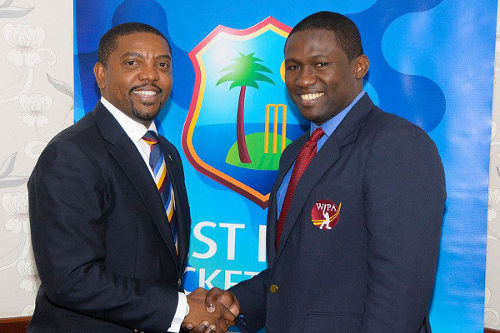 Photo: West Indies Players Association (WIPA) president Wavell Hinds (right) and West Indies Cricket Board (WICB) president Dave Cameron shake hands over the players'  controversial CBA/MOU in September 2014. (Courtesy WIPA)