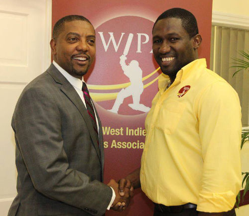 Photo: WIPA president Wavell Hinds (right) and WICB president Dave Cameron exchange pleasantries at the opening of WIPA's new office in Jamaica in 2014. (Courtesy WIPA)