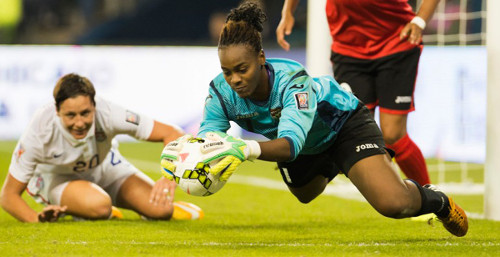 Photo: Trinidad and Tobago goalkeeper Kimika Forbes (right) holds on to the ball while United States attack Abby Wambach looks on. (Copyright AFP 2014)