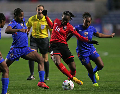 Photo: Trinidad and Tobago midfielder Karyn Forbes (centre) tries to weave past some Haiti players. Karyn and goalkeeper Kimika Forbes are sisters. (Copyright AFP 2014)