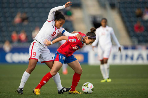 Photo: Trinidad and Tobago captain Maylee Attin-Johnson (left) tries to win the ball from Costa Rica striker Carolina Venegas during the 2014 CONCACAF Championship semifinal. (Courtesy CONCACAF)