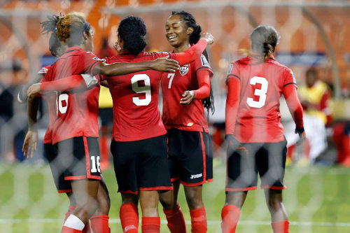 Photo: Trinidad and Tobago captain Maylee Attin-Johnson (number 9) is congratulated by Dernelle Mascall (second from right) and her teammates after her successful penalty kick against Guatemala in 2015 World Cup qualifying action. (Courtesy CONCACAF)