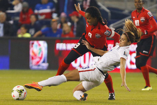 Photo: Trinidad and Tobago captain Maylee Attin-Johnson (left) tussles with United States attacker Alex Morgan (centre) while Tasha St Louis looks on in Kansas City. Trinidad and Tobago lost its 2014 CONCACAF opener 1-0. (Courtesy Kyle Rivas/AFP)