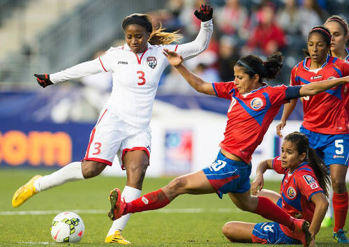 Photo: Trinidad and Tobago striker Mariah Shade (left) has her shot closed down by Costa Rica player Wendy Acosta in the 2014 CONCACAF Championship semifinal. (Courtesy CONCACAF)