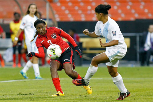Photo: Trinidad and Tobago striker Mariah Shade (left) shoots past Guatemala defender Londy Barrious but also just wide of the far corner during the 2014 CONCACAF Championship. (Courtesy CONCACAF)