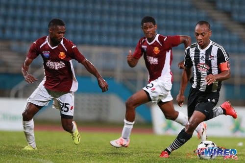 Photo: Central FC midfielder and captain Leston Paul (right) runs at North East Stars players Keryn Navarro (left) and Taryk Sampson during the 2014 First Citizens Cup final. (Courtesy Allan V Crane/Wired868)