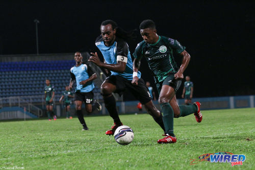 Photo: W Connection and Trinidad and Tobago national under-20 winger Akeem Garcia (right) takes on WASA FC captain Akil Harley in 2014 Toyota Classic action. (Courtesy Sinead Peters/Wired868)