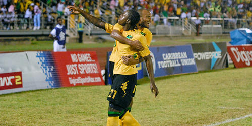Photo: Jamaica striker Darren Mattocks (foreground) and captain Rodolph Austin are Caribbean champions. (Courtesy CONCACAF)
