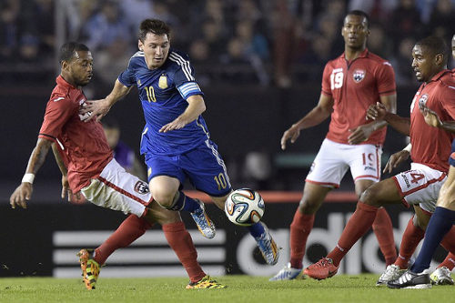 "Photo: Argentina captain and superstar Lionel Messi (centre) dribbles between Trinidad and Tobago players Lester Peltier (far left), Andre Boucaud (far right) and Carlyle Mitchell during an international friendly in Buenos Aires on 4 June 2014. Argentina won 3-0. Trinidad and Tobago and Argentina could meet again if the ""Soca Warriors"" qualify for the 2016 Copa America Centenario. (Copyright AFP 2014/Daniel Garcia)"