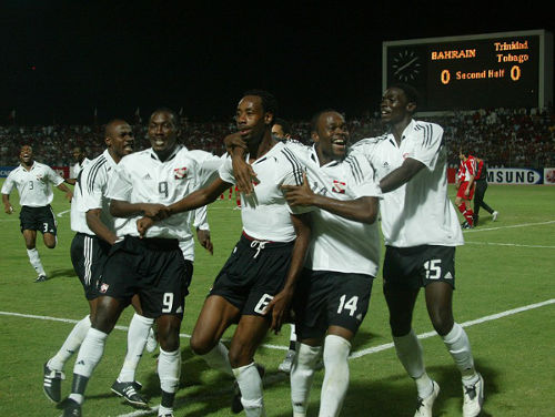 Photo: Stern John (second from right) celebrates with goal scorer Dennis Lawrence (centre), Kenwyne Jones (far right), Aurtis Whitley (second from left) and Cyd Gray after going ahead against Bahrain on November 16, 2005. (Copyright AFP 2014)