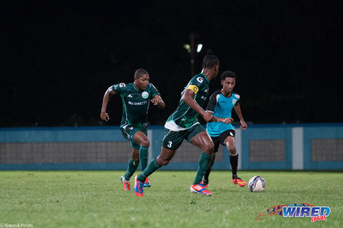 Photo: WASA attacker Mario Kissoon (right) runs at W Connection captain Gerard Williams (centre) and Mekeil Williams during the 2014 Toyota Classic Cup. (Courtesy Sinead Peters/Wired868)