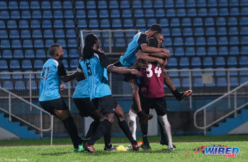 Photo: WASA and ex-Trinidad and Tobago striker Stern John (right and partially hidden) is swarmed my teammates after scoring the winning penalty against DIRECTV W Connection in the Toyota Classic Cup preliminary round. (Courtesy Sinead Peters/Wired868)