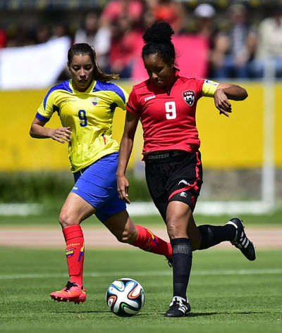 Photo: Trinidad and Tobago midfielder and captain Maylee Attin-Johnson (right) advances with the ball under pressure Ecuador star Gianina Lattanzio during the first leg of the FIFA Play Off in Quito. (Copyright AFP 2014/Rodrigo Buendia)
